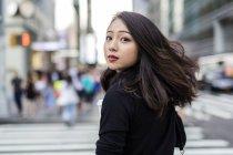 Portrait de jeune femme regardant par-dessus l'épaule à la rue — Photo de stock