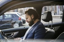 Businessman using cell phone in a car — Stock Photo