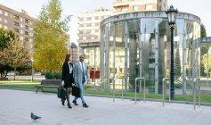 Jeune homme d'affaires et femme d'affaires, promenade dans la ville — Photo de stock