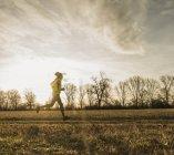 Ritratto di un giovane che corre sul campo — Foto stock