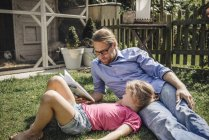 Father reading book with daughter in garden — Stock Photo