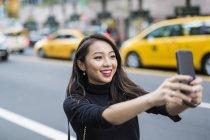 Портрет молодої жінки, беручи selfie на вулиці — стокове фото