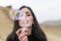 Woman blowing soap bubbles — Stock Photo