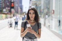 Portrait de jeune femme utilisant un smartphone dans la rue — Photo de stock