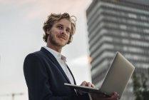 Empresario usando portátil al aire libre y mirando hacia los lados - foto de stock