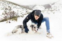 Asturias, España, joven acariciando a su perro en la nieve - foto de stock