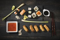 Top view of sushi set on dark background served with soy sauce — Stock Photo