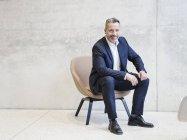 Empresário sentado em poltrona — Fotografia de Stock