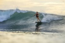 Indonesia, Bali, woman surfing on a wave — Stock Photo