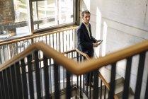 Portrait d'homme d'affaires debout avec tablette sur escalier — Photo de stock