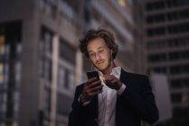 Geschäftsmann in der Dämmerung mit Handy in der Stadt — Stockfoto