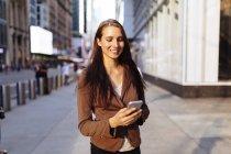 Joven empresaria con smartphone en la calle de Manhattan. Ciudad de Nueva York. Nos - foto de stock