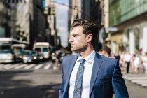 Uomo d'affari che cammina sulla strada in città — Foto stock