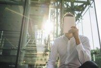 Porträt eines Geschäftsmannes, der Gesicht mit Notizbuch verschließt — Stockfoto