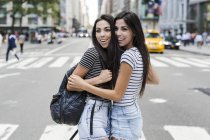 Twin sisters standing on zebra crossing — Stock Photo
