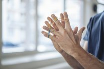 Cropped view of male hands with rubber bands on fingers — Stock Photo