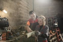 Couple working in farm workshop, using bench vice — Stock Photo