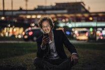 Sonriente hombre de negocios sentado en el Prado al anochecer con teléfono celular y los auriculares - foto de stock