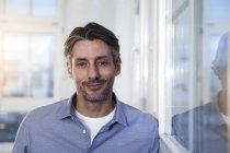 Retrato de homem sorridente olhando para a câmera no escritório — Fotografia de Stock