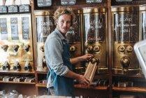 Sacchetto di riempimento torrefattore di caffè con caffè in negozio — Foto stock