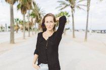 Усміхаючись молоду жінку, ходьба на набережній — стокове фото