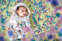Happy baby girl lying surrounded by colorful confetti — Stock Photo