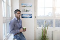 Portrait of smiling man with cup of coffee standing in office — Stock Photo
