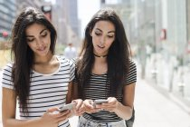 Twin sisters walking with cell phones — Stock Photo