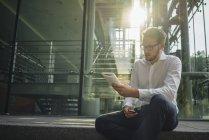 Portrait d'homme d'affaires détenant portable et smartphone — Photo de stock
