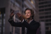 Businessman in the city at dusk using cell phone — Stock Photo