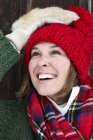 Portrait of smiling woman wearing red bobble hat and fur gloves in winter — Stock Photo