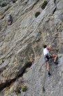 Pendant la journée arrière portrait de deux hommes, escalade sur paroi rocheuse — Photo de stock