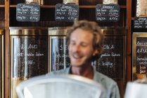 Assortment of coffee in coffee roastery and smiling coffee roaster on background — Stock Photo