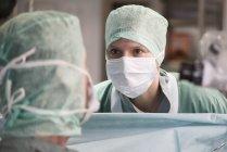 Обрезанное портрет мужского и женского пола хирургов в операционной комнате — стоковое фото