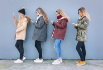 Four young women texting with smartphones in front of grey wall — Stock Photo