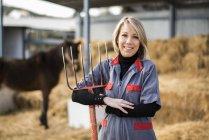 Agricultrice, tenant le chariot de foin à cheval sur fond — Photo de stock