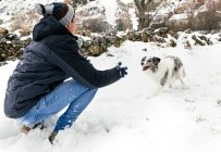 Leon, Spain, young man playing in the snow with his dog — Stock Photo