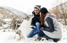 Jeune couple de Leon, Espagne, s'amuser avec leur chien dans la neige — Photo de stock