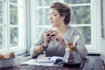 Giovane donna che beve caffè a tavola guardando attraverso la finestra — Foto stock