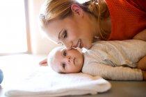 Mère heureuse embrassant bébé à la maison — Photo de stock