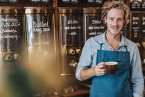 Portrait of smiling coffee roaster holding cup of coffee in shop — Stock Photo