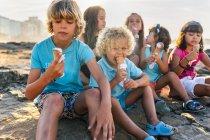 Groupe de six enfants mangeant de la crème glacée sur la plage — Photo de stock
