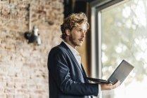 Бізнесмен проведення ноутбук і дивитися вбік — стокове фото