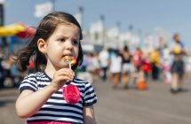 New York, Coney Island, Portrait of little girl with colorful lollipop over walkway in a sunny summer day — Stock Photo