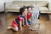 Twin brothers having fun in front of fan — Stock Photo