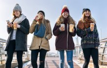 Four young women walking on bridge in the city with take away coffee — Stock Photo