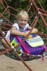Portrait of smiling little girl with school bag sitting in nest swing on playground — Stock Photo