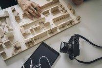 Ritagliata vista delle mani dell'uomo con la macchina fotografica e modello di distretto in legno — Foto stock