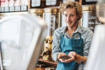Portrait of coffee roaster in shop holding coffee beans and looking at camera — Stock Photo