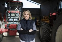Woman standing in rural tractors warehouse and looking at camera — Stock Photo